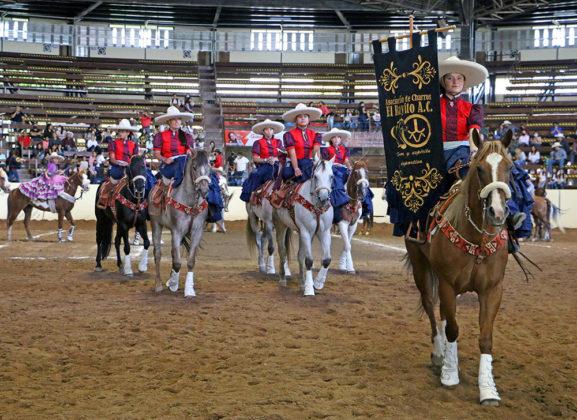 La escaramuza El Rayito de Coahuila, precedida por su estandarte, realizando una buena actuación en la primera competencia del lunes