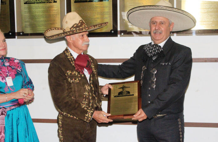 El homenajeado recibe una réplica de la placa conmemorativa de manos del presidente de la Federación, ingeniero Leonardo Dávila